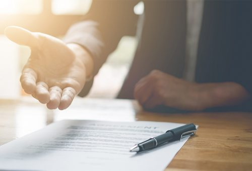 Courtier immobilier avec contrat qui tend la main